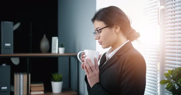 Side view üzleti nő élvezi forró kávé az irodában