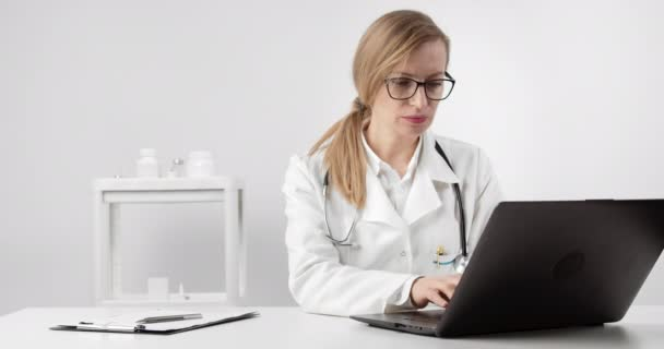 Female doctor in medical uniform working on laptop