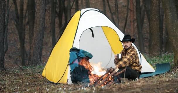 Nyugodt ember tüzet csinál a sátor közelében