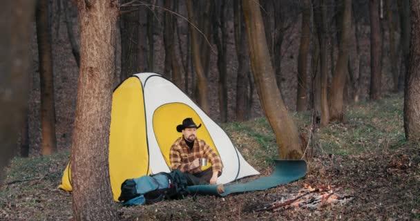 Muž odpočívající poblíž požáru v lesním táboře
