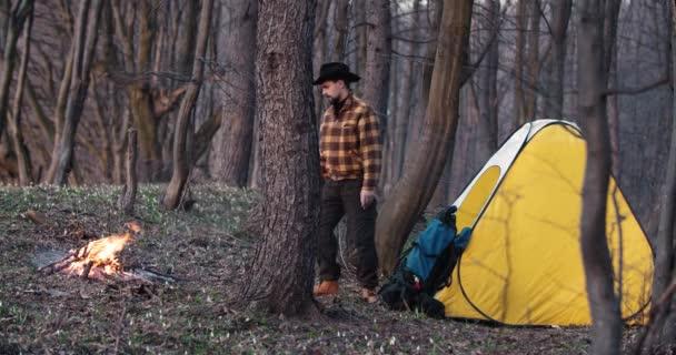 Muž odpočívající poblíž ohně v táboře