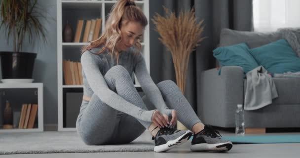 Fitness-Frau bindet Schnürsenkel zu Hause an Turnschuhe
