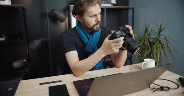 Bärtiger Mann überprüft Fotos zur Retusche auf Laptop