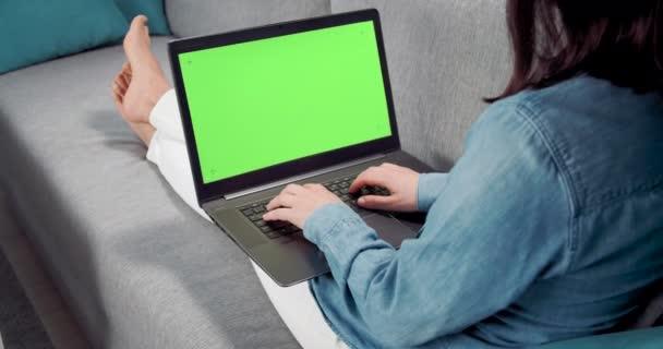 Zadní pohled ženy relaxující na gauči s osobním notebookem