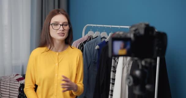 Usmívající se dáma mluví před kamerou o trendech v oblečení