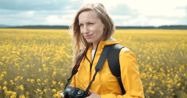 Nő használja kamera forgatás mező virágok