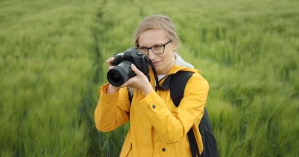 Idős nő sárga dzsekiben képeket készít a búzamezőről.
