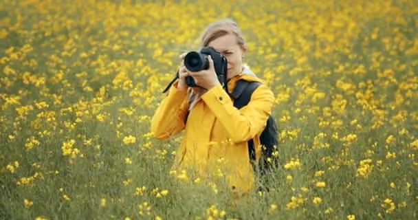 Šťastná dáma používající digitální fotoaparát pro focení terénu