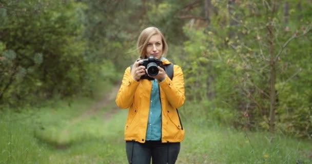 Ženský fotograf fotografující zelený les
