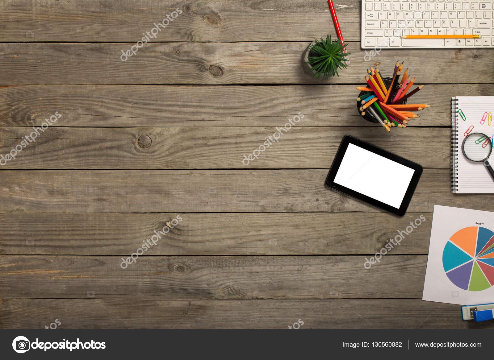 Tablette avec écran blanc sur le bureau en bois avec des objets de