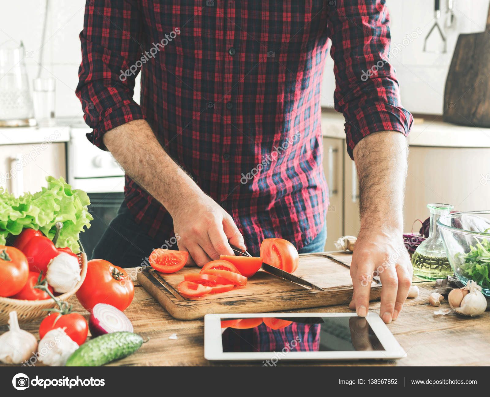 Man following recipe on tablet and cooking healthy food stock man following recipe on tablet and cooking healthy food stock photo forumfinder Gallery