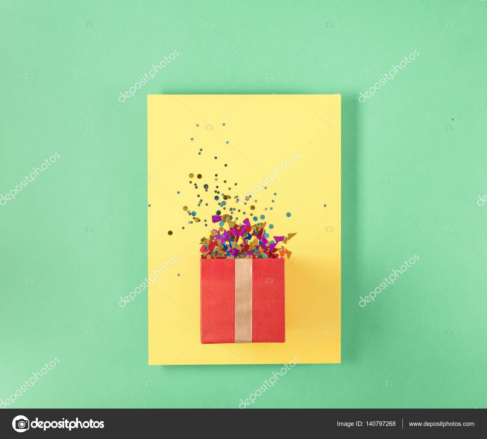 Caja de regalo roja con varios confeti de fiesta en tarjeta amarilla ...