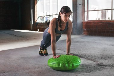 Woman athlete push ups on a gymnastic ball