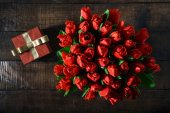 Pohled shora kytice červené tulipány s červené krabičky na tmavý dřevěný stůl s kopií prostor