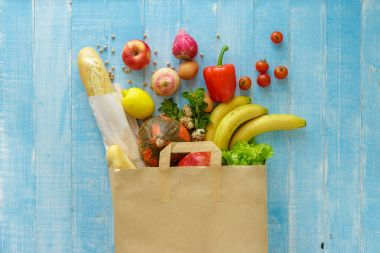 Paper bag full of different healthy food on blue background. Top view. Flat lay
