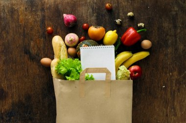 Paper bag of different health food and notebook on wooden background. Top view. Flat lay