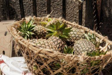 Heap pineapples in straw basket market stone town, Tanzania, Zan