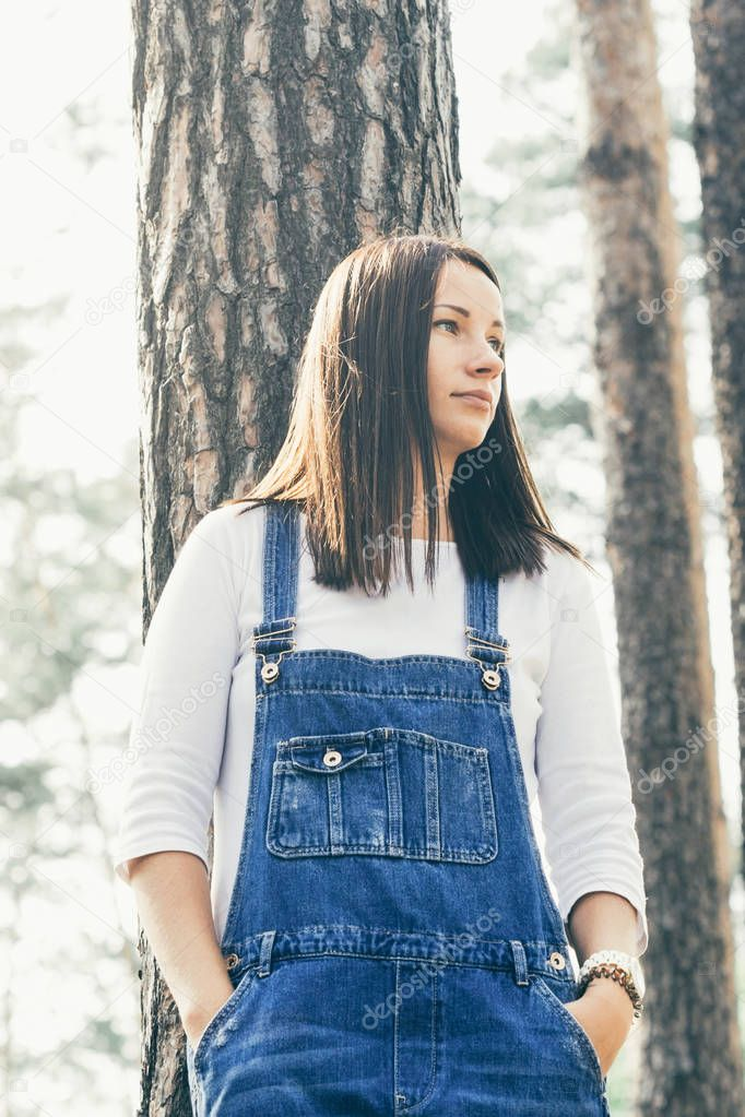 Beautiful young woman in jeans overalls standing in woodland at sunny day