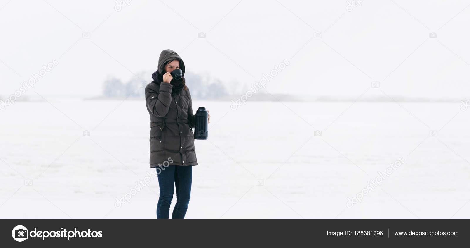 Γυναίκα το χειμώνα ρούχα στέκεται στο χιόνι και να πίνει καφέ από το  θερμός– εικόνα αρχείου 67720fd93a5