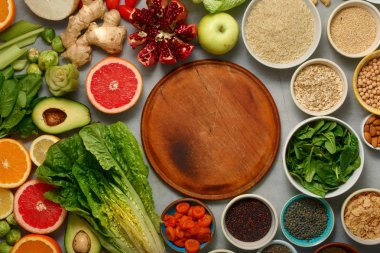 Around wooden kitchen board set clean eating. Vegetarian healthy food - different vegetables and fruits, superfood, seeds, cereal, leaf vegetable on gray background top view Flat lay