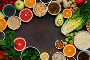 Frame of vegetarian healthy food - different vegetables and fruits, superfood, seeds, cereal, leaf vegetable on dark background, top view. Flat lay. Clean eating concept