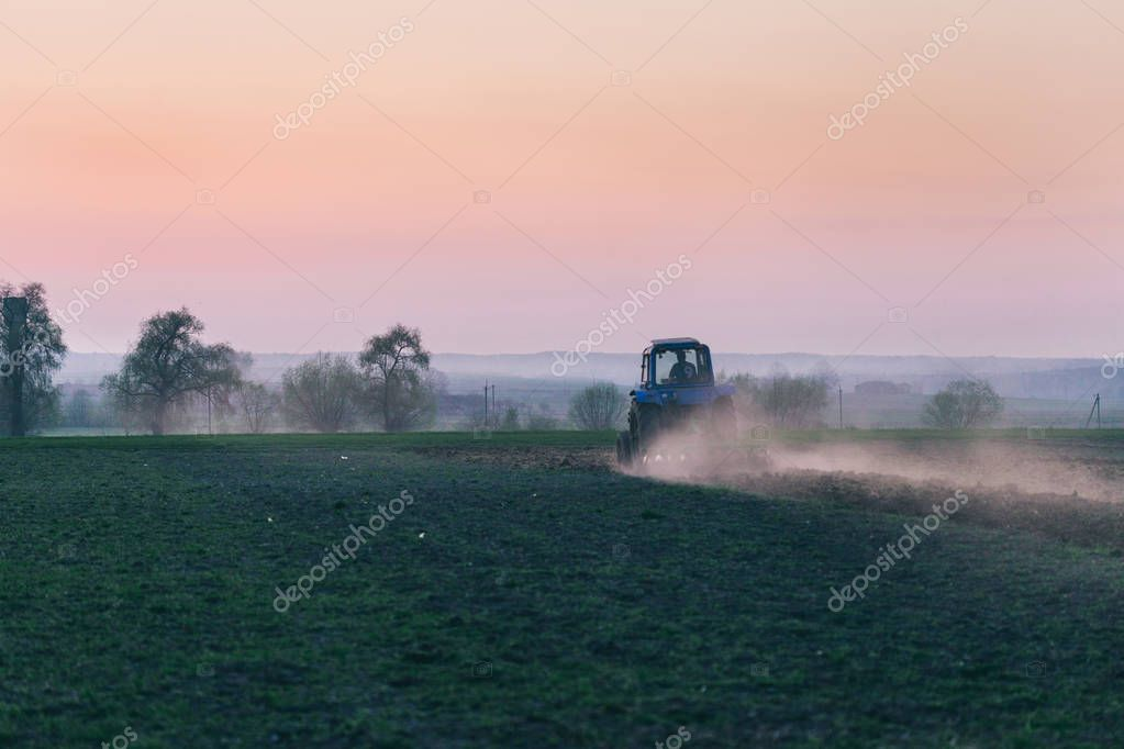 Scenic view of agricultural machinery in field at sunset