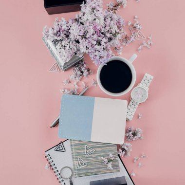 Office table desk with cup coffee, notebook, bouquet lilac, pen, watches and clips. Top view. Flat lay. Home office workspace. Women's office accessories on pink background