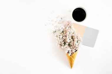 Top view ice cream cone with branch white lilacs, cup coffee and empty postcard on white background with copy space. Minimal spring concept. Flat lay