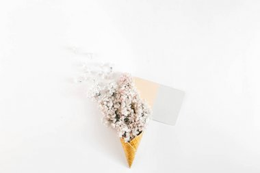 Top view ice cream cone with branch white lilacs and empty card on white background. Minimal spring concept. Flat lay