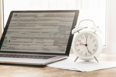 Tax Time Concept. laptop with form individual income tax returns with alarm clock