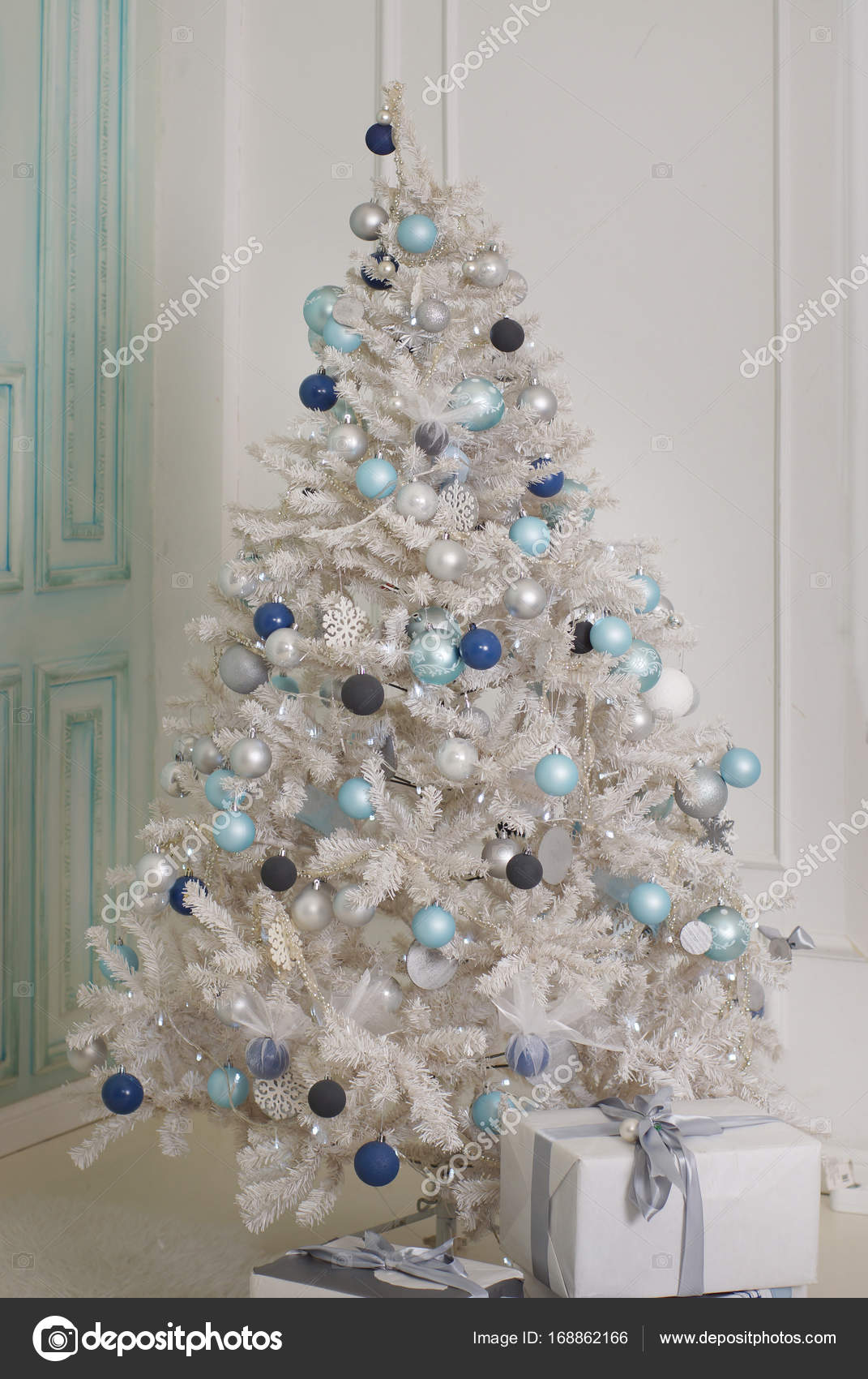 a decorated christmas tree stands near a bright wall artificial white spruce with blue balls and garlands photo by morele
