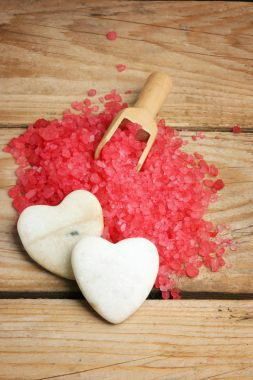 White stones in the form of hearts on a hill of red salt for a bath, romance in a spa salon