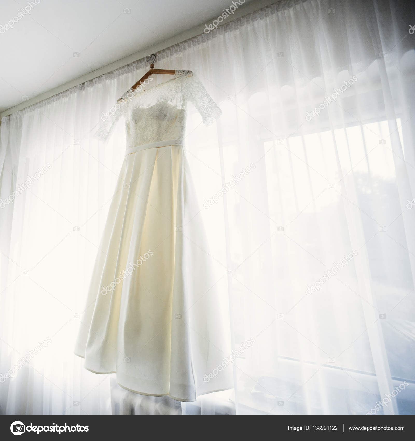 5d35076640a Lace bridal gown by window — Stock Photo © olexiysyrotkin  138991122