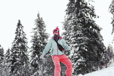 Woman snowboarding down the hill