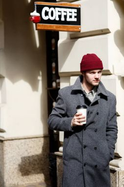 Man in red hat with coffee on the street
