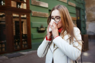 Woman sneezes standing on the street
