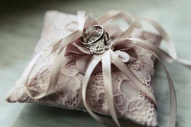 Wedding rings made of white gold lie on pink pillow