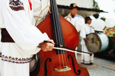 Man in ethnic Ukrainian suit plays on the cello