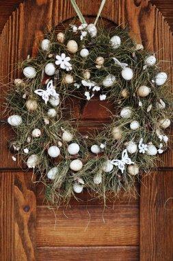 Wreath of white eggs and hay hangs on the door