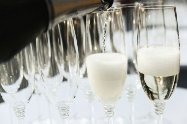Man pours champagne in the glasses on dinner table