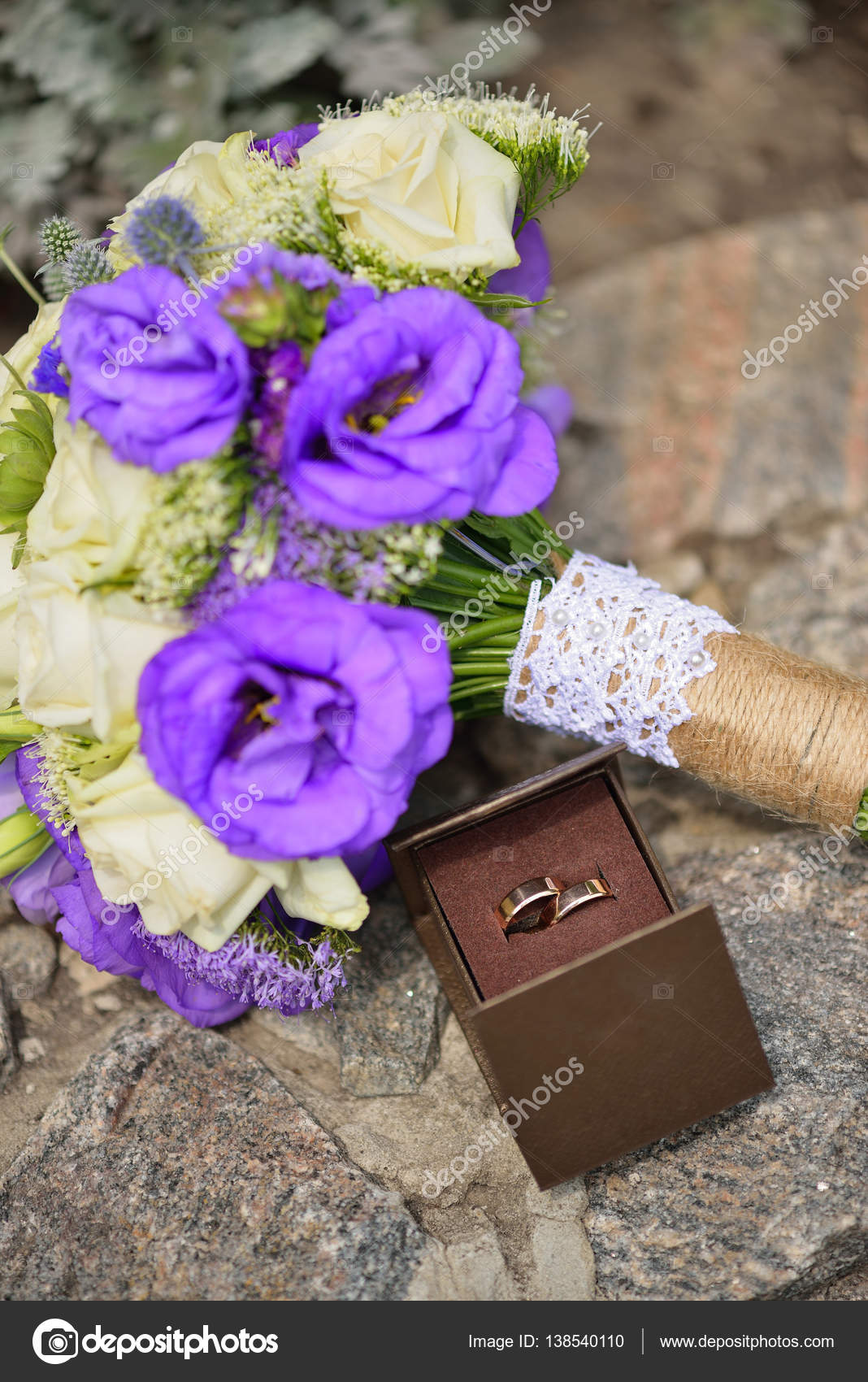 Close up of wedding bouquet with white purple flowers and gold close up of wedding bouquet with white and purple flowers and gold rings in brown box on stone floristic conmosition photo by okkate izmirmasajfo