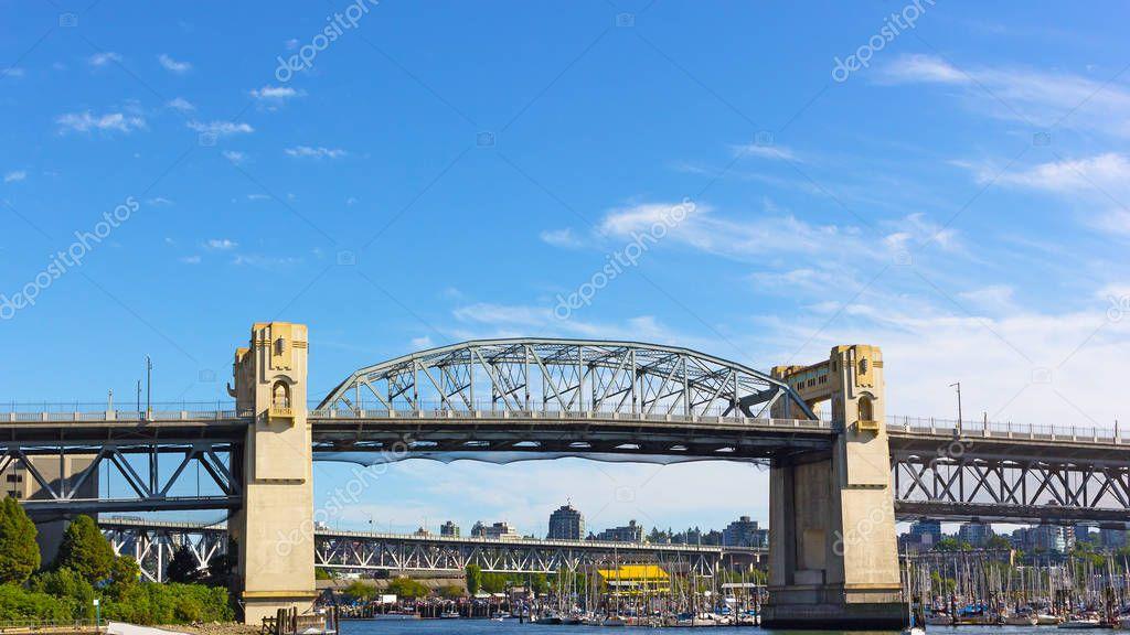 Burrard Bridge in the morning in Vancouver, British Columbia, Canada. Steel truss bridge over False Creek with imposing concrete towers.