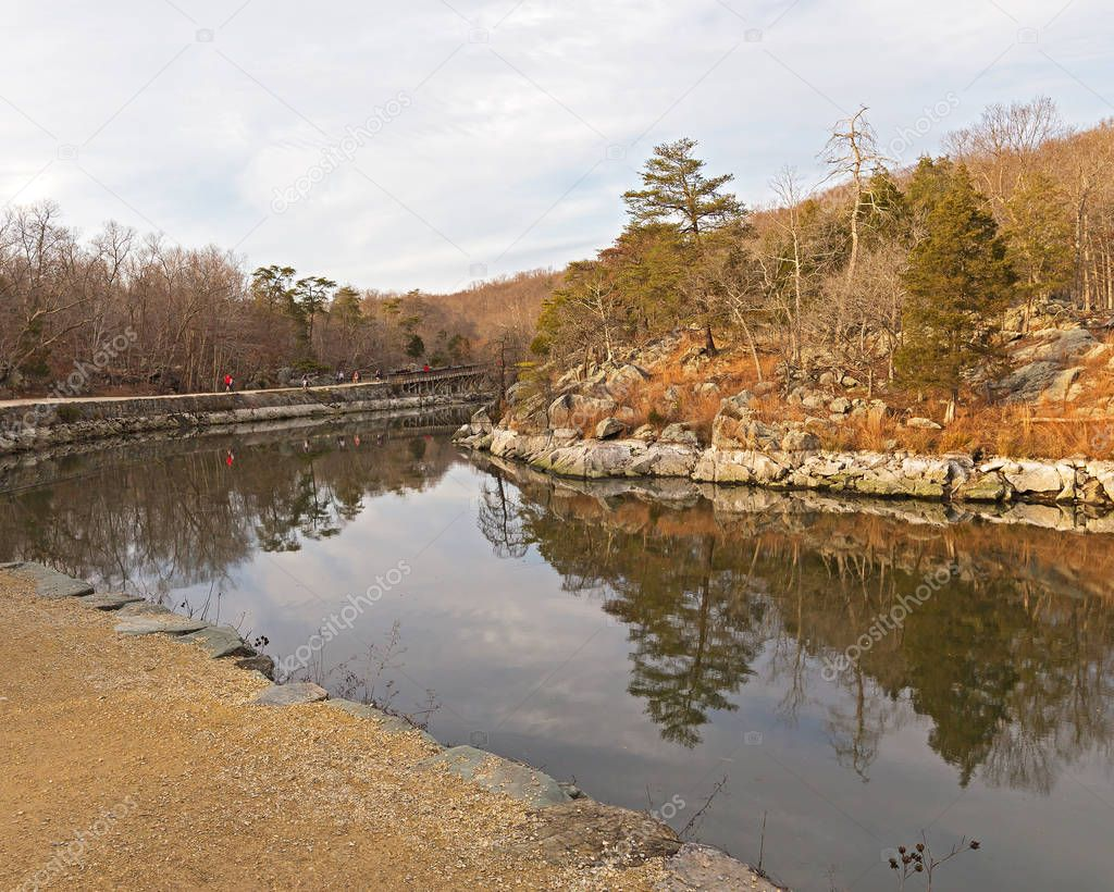 Scenic winter landscape along the canal with footpath and rocky banks. Forest landscape with trees reflection in canal waters.