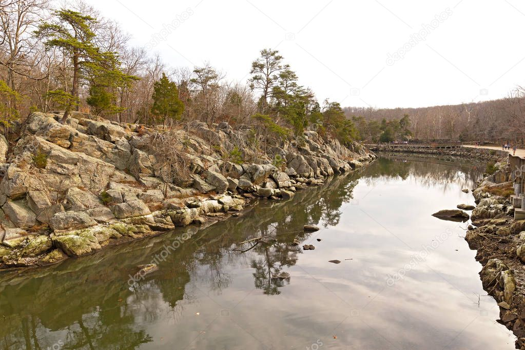 Rocky banks of the canal along Potomac River with footpath. Winter forest landscape with trees reflection in canal waters.