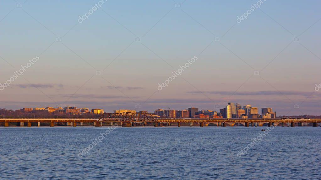Washington DC panorama across Potomac River at sunrise. Transport artery connecting downtown with Virginia suburbs of metropolitan area.