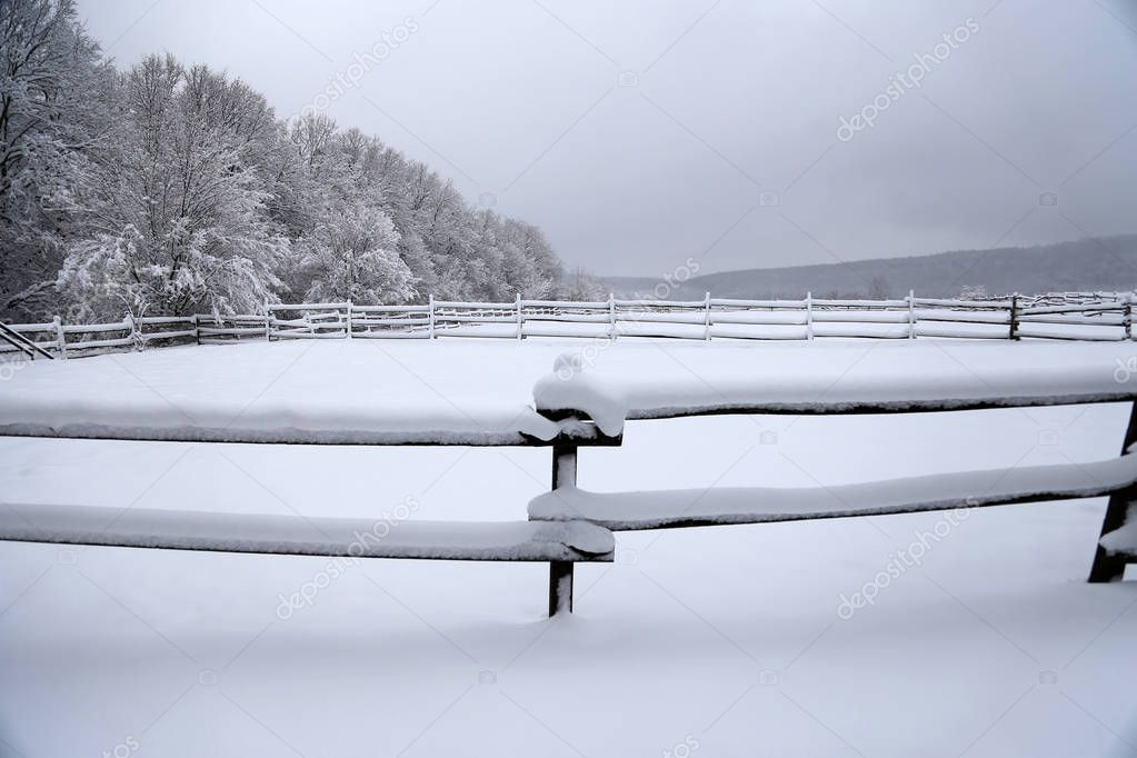 Fabulous winter landscape with fresh snow on rural wooden fence at animal farm