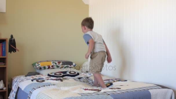 peuter springt op zijn bed in de slaapkamer stockvideo