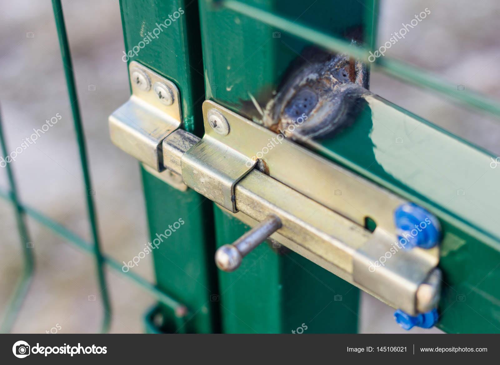 Serrure porte vert jaune. Porte de la grille. Clôture autour du ...