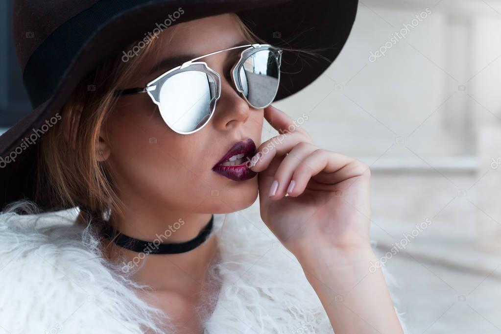 433a5d373eb Closeup portrait of young beautiful fashionable woman with sunglasses. Lady  posing on dark grey background. Model wearing stylish wide-brimmed hat