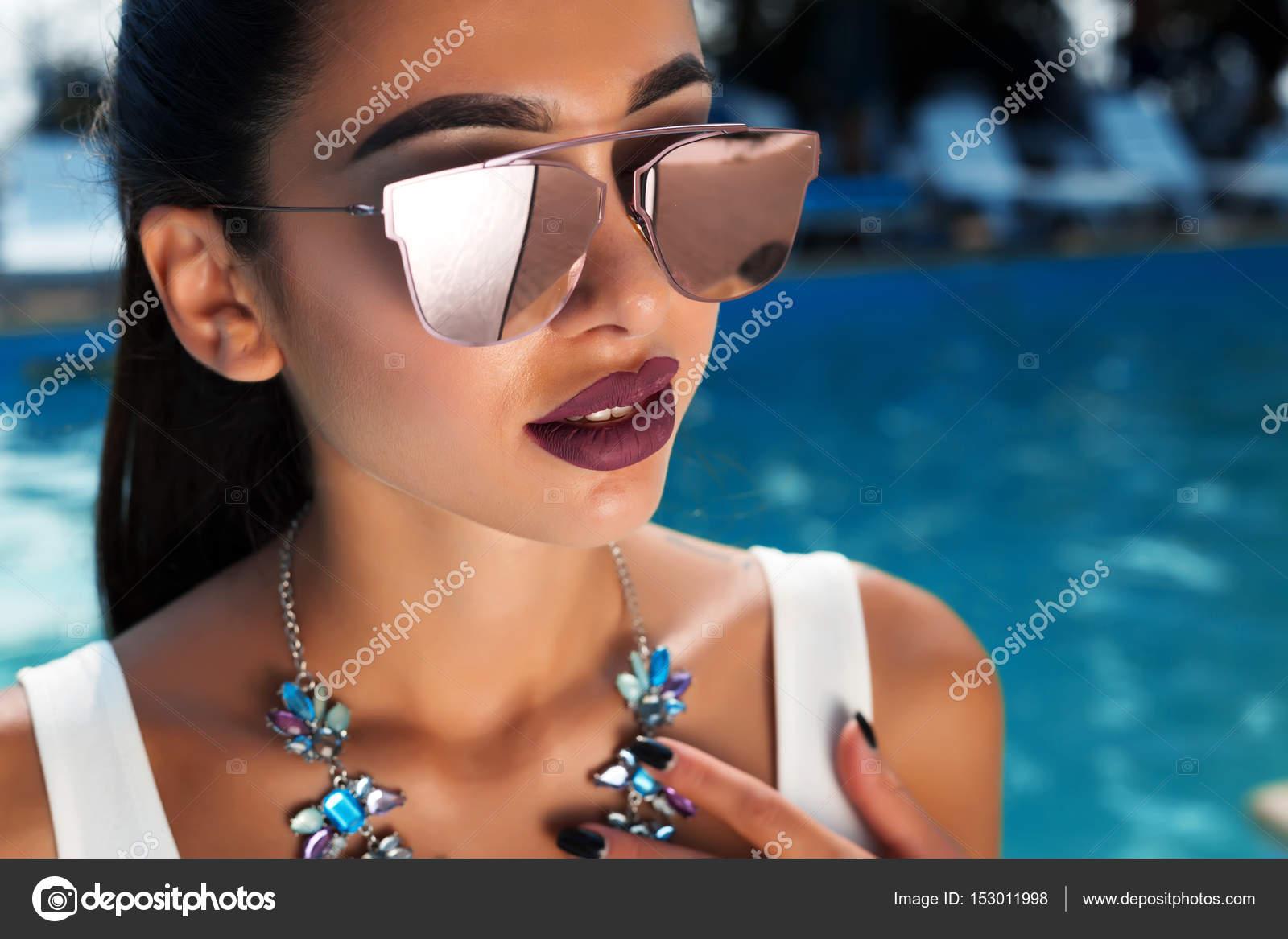 f9968444c8666 Moda verão fechar retrato da bela mulher sexy moda praia elegante branca e  óculos de sol espelhados com colar perfeito e penteado no fundo da piscina  ...